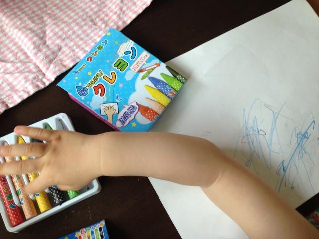 クレヨンと紙と子供の腕