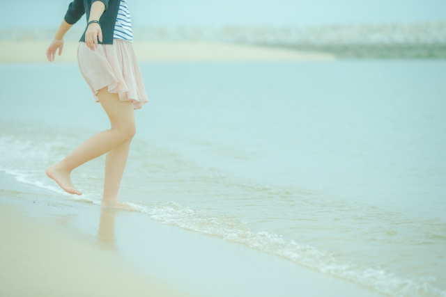 波打ち際で楽しく遊ぶ女性