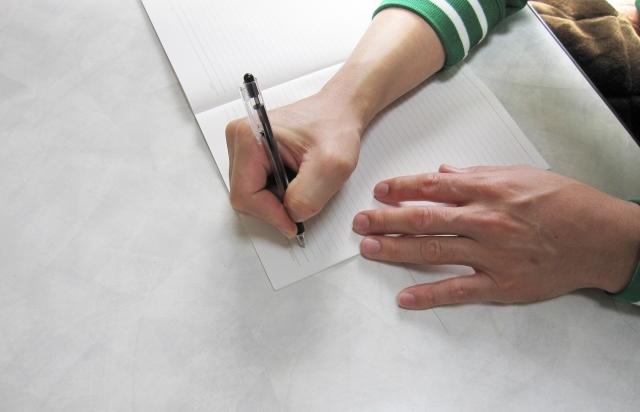ボールペンでノートに書く男性