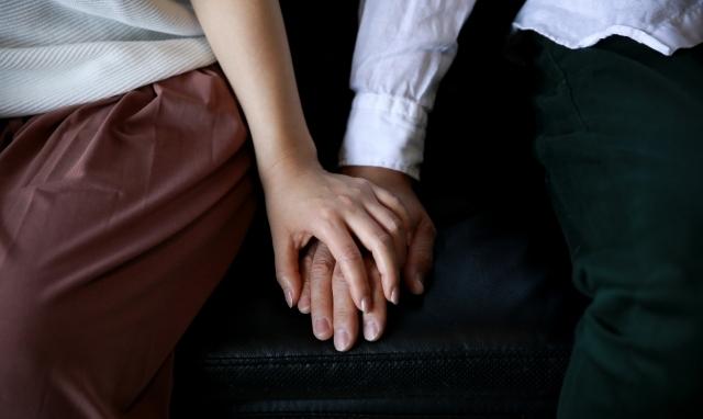 ソファーで手をつなぐ男女